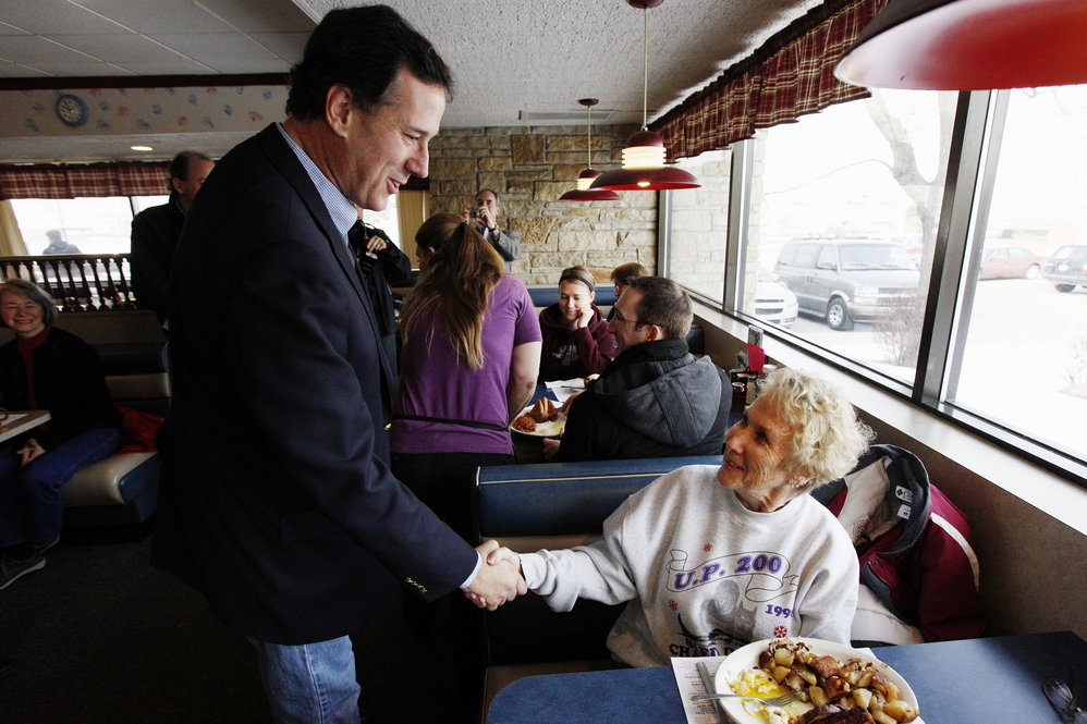 Santorum greets diners at New Beginnings Restaurant in Kentwood, Mich. He lost Tuesday but is atop polls in several states with March 6 primaries.