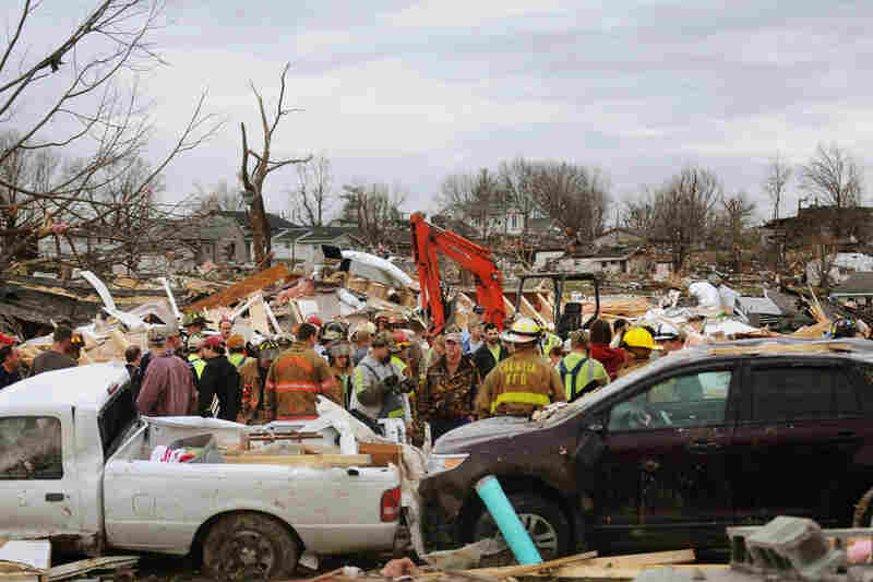 Emergency responders work to clear debris in a Harrisburg, Ill., neighborhood after a powerful storm lashed the Midwest on Wednesday.
