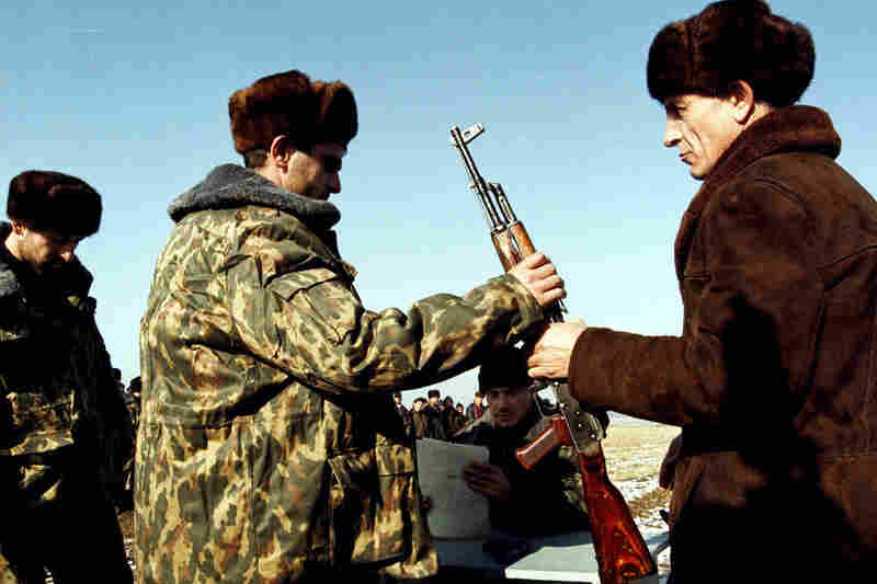Russian commanders gave Kalashnikov rifles to Chechen militiamen who helped in the fight against Islamic militants in 1999.