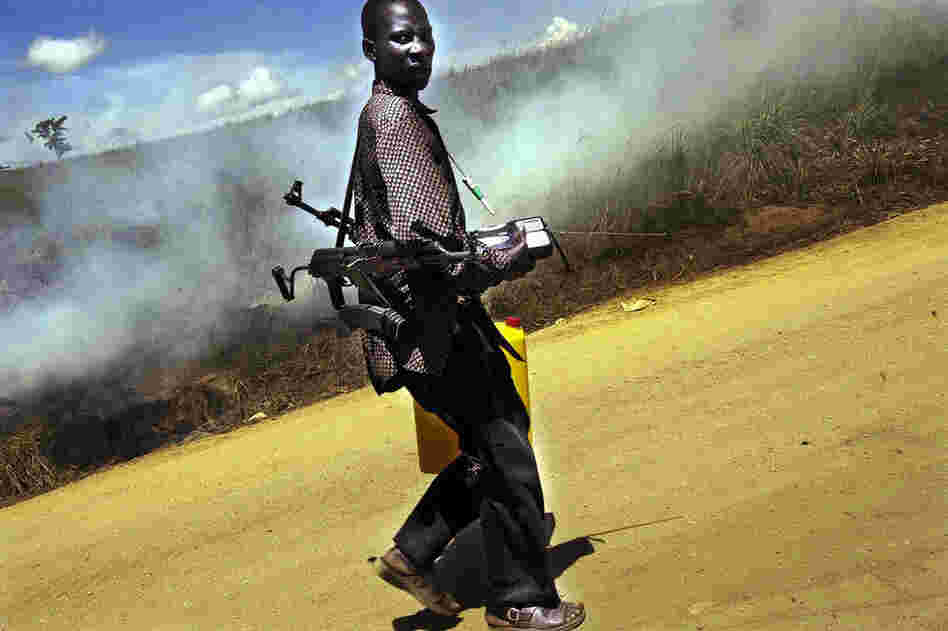 A Congolese fighter carries two AK-47s past burning bushes following strife in the Ituri region of the Democratic Republic of Congo in 2003.