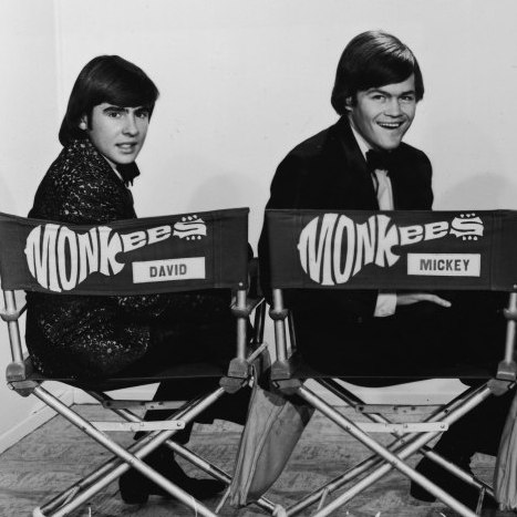 Promotional portrait of popular music and television group the Monkees, dressing in tuxedos and they as they sit in folding chair and look over their shoulders, early 1970s. From left, British musician and actor Davy Jones, and American musician and actors Mickey Dolenz, Peter Tork, and Michael Nesmith.