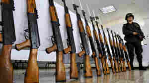 A Colombian police officer stands guard next to seized Chinese-made AK-47 replicas on Nov. 18, 2009. The guns have become so ubiquitous around the world that Russia's planned redesign may not do much to booster sales.