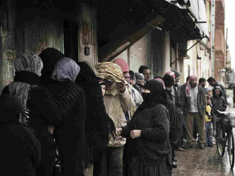 Syrians line up for bread outside a bakery in Qusayr on Thursday. After a month of heavy fighting in parts of Homs, civilians describe the conditions as miserable.