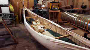 Goudie's last canoe hangs next to the form used to mold the wood. The unfinished canoe is weighted down with sandbags to keep the canvas taut.