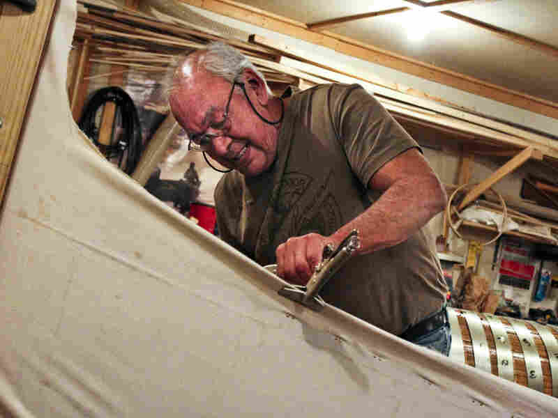 Joe Goudie uses clamps to stretch the canvas tightly before nailing it to the canoe's wooden frame. The task takes three pounds of brass tacks.