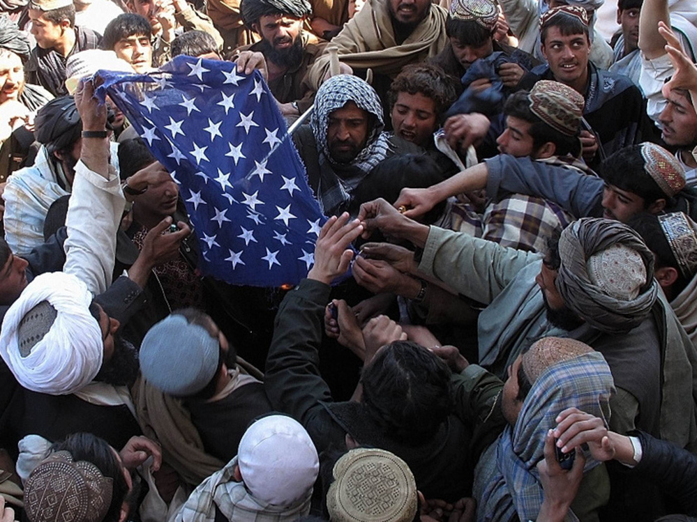 Feb. 23: Afghan demonstrators burn a U.S. flag during a protest in Afghanistan's Helmand province.