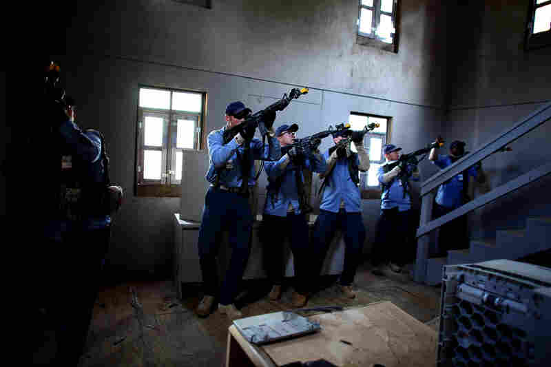 Role-players dressed as Afghan policemen clear a mosque in the mock village where a sniper had been firing at them.
