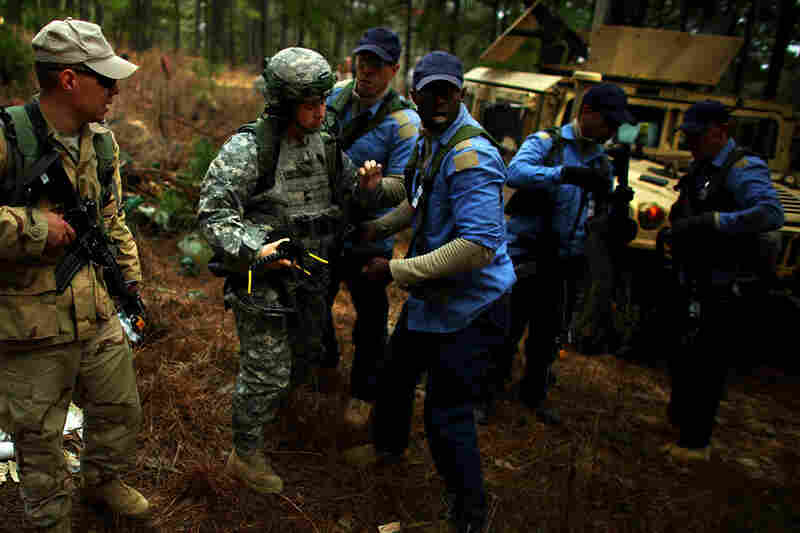 Role-players from the Afghan National Army, in tan, and Afghan National Police, in blue, help an injured American soldier.