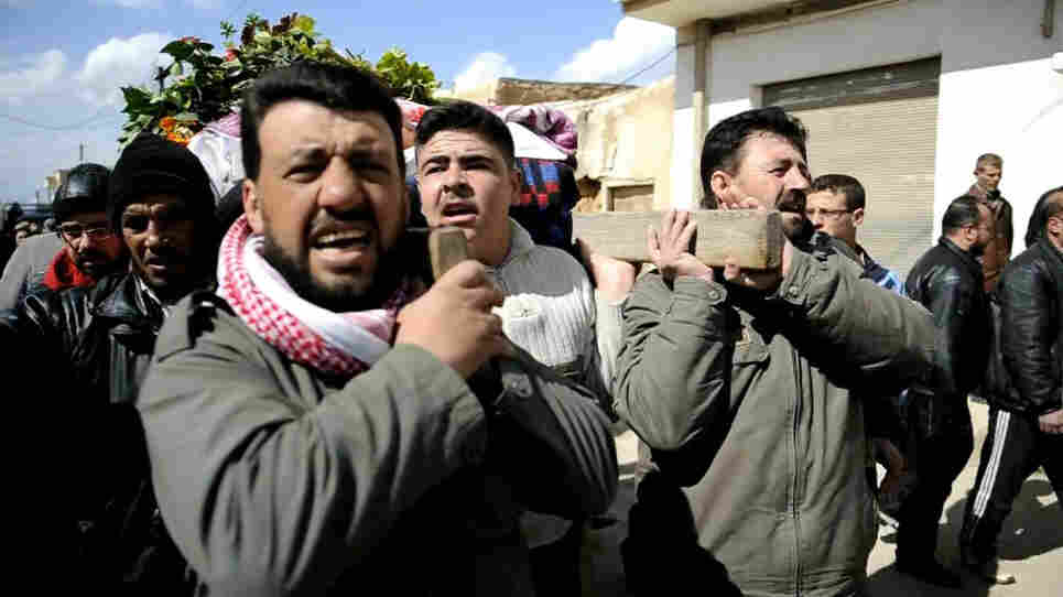 Syrian mourners on Wednesday carried the body of a man who was killed in fighting near Homs.