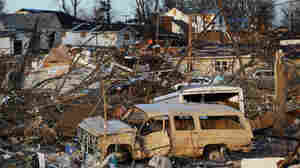 Vehicles and other possessions lie scattered in Harrisburg, Ill.