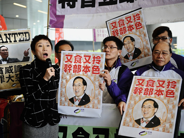 Protesters hold up signs criticizing Hong Kong's Chief Executive Donald Tsang outside the island's Parliament, March 1. Tsang has been embroiled in controversy over his alleged ties to rich tycoons.
