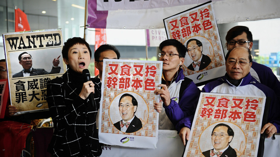 Protesters hold up signs criticizing Hong Kong's Chief Executive Donald Tsang outside the island's Parliament, March 1. Tsang has been embroiled in controversy over his alleged ties to rich tycoons.   (AFP/Getty Images)