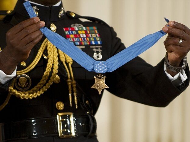 A military aide holds up the Congressional Medal of Honor. The 2005 Stolen Valor Act makes false claims about receiving military medals punishable by up to one year in prison.