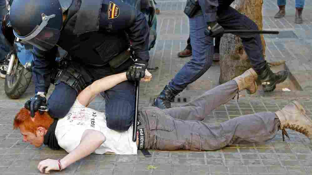 Police restrain a student protesting against education cuts during a rally in Valencia, in eastern Spain, on Feb. 20. Spaniards are beginning to feel the effects of $20 billion in austerity measures, and discontent is growing.
