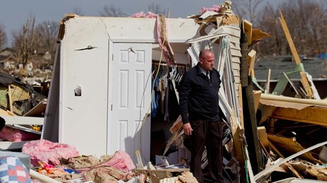 Steve McDonald stands in the debris from the home of his mother-in-law, Mary Osman, who died when a tornado touched down Wednesday in Harrisburg, Ill. She was one of five people killed on Brady Street.