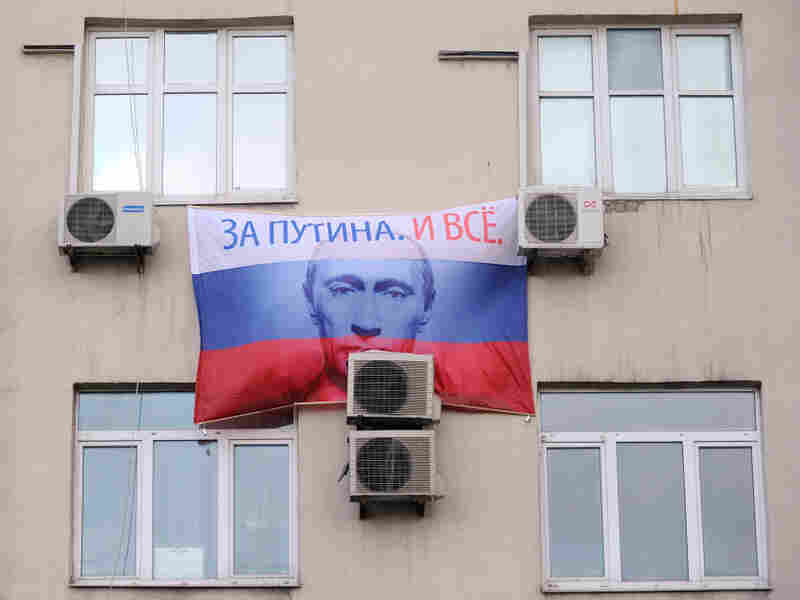 """A portrait of Russian prime minister and presidential candidate Vladimir Putin, bearing the slogan """"For Putin! And That's It!"""" hangs on a building in Moscow."""