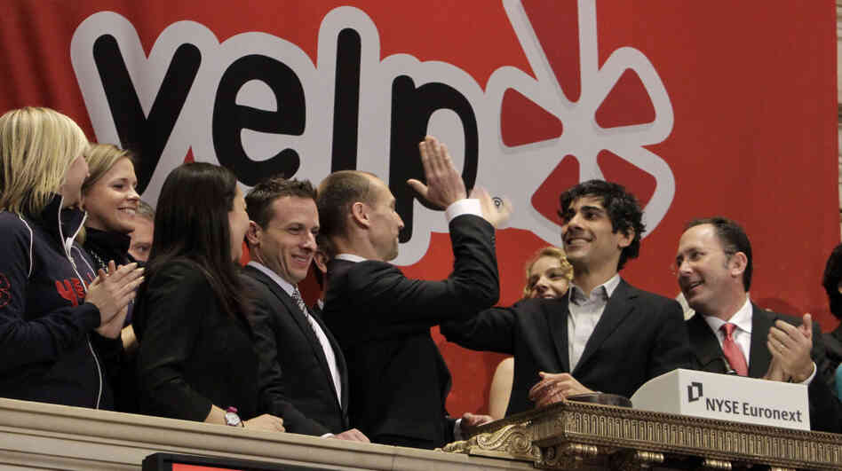 Jeremy Stoppelman, second from right, Yelp co-founder and CEO, gets a high-five during opening bell ceremonies of the New York Stock Exchange on Friday.