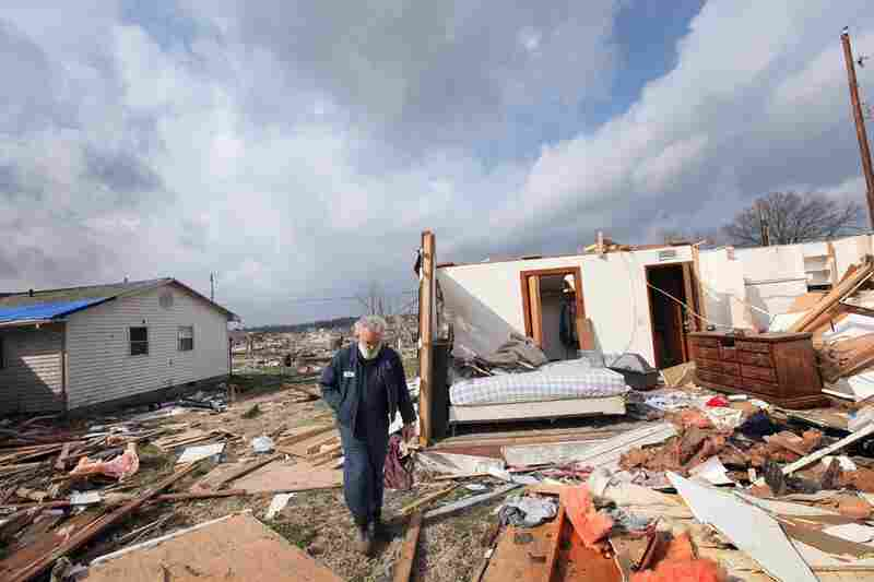 Keith Huke walks past his tornado-ravaged home in Harrisburg, Ill., on Friday. Huke escaped without any injuries.