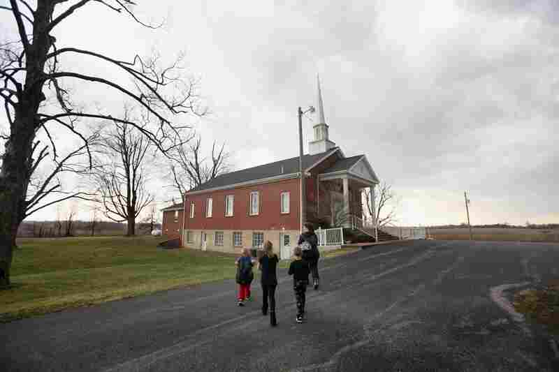 Tina Wellham takes her children to the basement of the New Bethel Baptist Church as a tornado warning sounds near Fredonia, Ky.