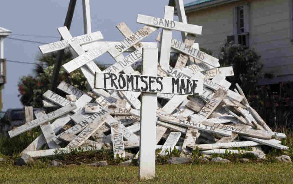 "A cross with the words ""Promises Made""-- referring to statements from BP and government officials — stands in front of a pile of crosses symbolizing things that were impacted by the spill, in a front yard in Grand Isle, La."