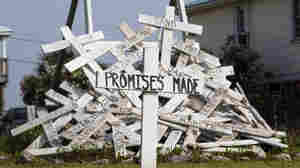 """A cross with the words """"Promises Made""""-- referring to statements from BP and government officials — stands in front of a pile of crosses symbolizing things that were impacted by the spill, in a front yard in Grand Isle, La."""