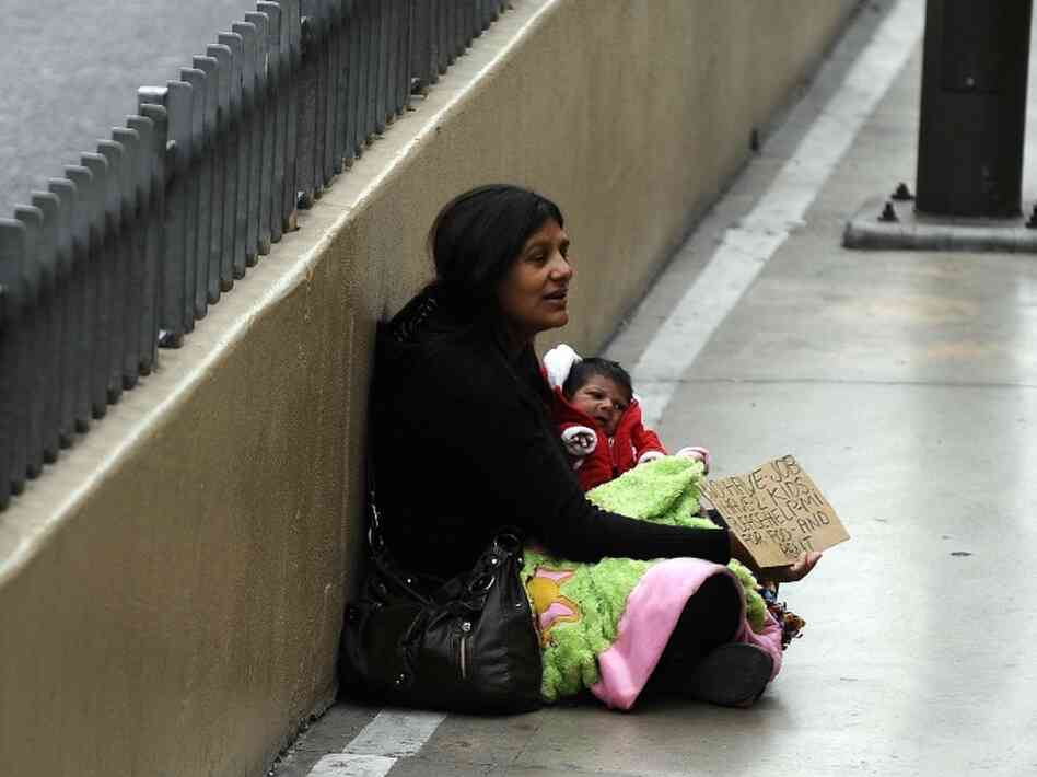 A woman begs for alms along the Las Vegas strip in Las Vegas, Nevada, on Nov. 11, 2011. While official unemployment rates for women dipped less than for men during the recession, they have recovered slower.