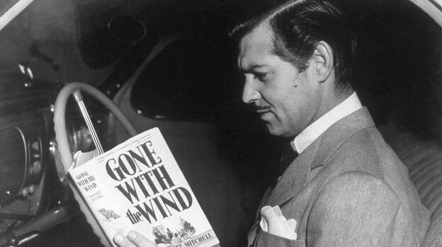 Clark Gable (as Rhett Butler) reading the novel 'Gone With the Wind' by Margaret Mitchell.