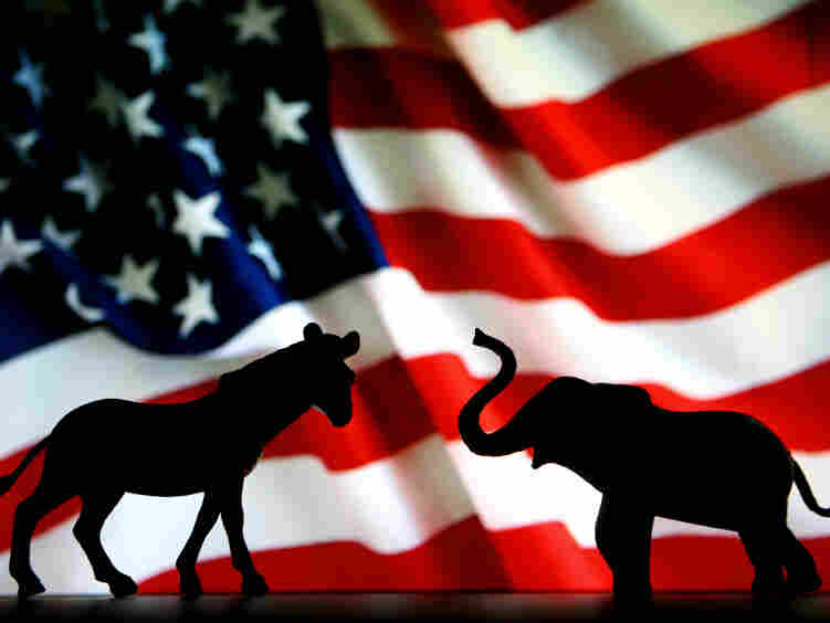 The symbols of the two political parties, the donkey for the Democrats and the elephant for the Republicans, battle it out in front of the American flag.