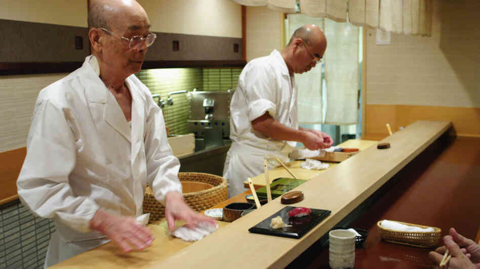 Jiro Ono (left) owns and runs a celebrated sushi restaurant in a Tokyo basement. His oldest son, Yoshikazu, waits to take over the world-famous family business.