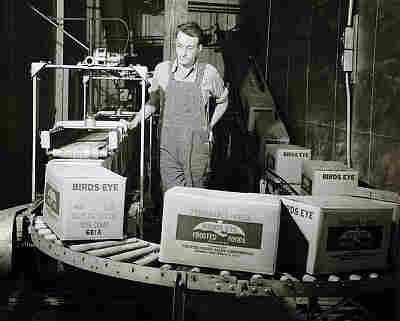 Worker surveys boxes of Bird's Eye frozen foods as they move along a conveyor belt circa 1922-1950.