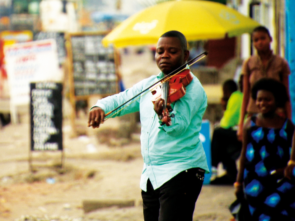 A member of the Orchestre Symphonique Kimbanguiste plays outdoors in Kinshasa, Democratic Republic of Congo.