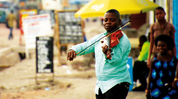 A member of the Orchestre Symphonique Kimbanguiste plays outdoors in Kinshasa, Democratic Republic of Congo. (courtesy of the artists)