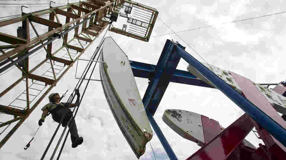 A worker hangs from an oil derrick near Williston, N.D. The state now produces 500,000 barrels of crude oil per day, and production continues to rise.