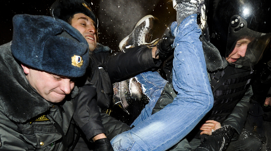 Police officers detain one of the protesters at Moscow's Pushkin Square on Monday. The demonstrators gathered to protest Vladimir Putin's win in Sunday's presidential election. (AFP/Getty Images)