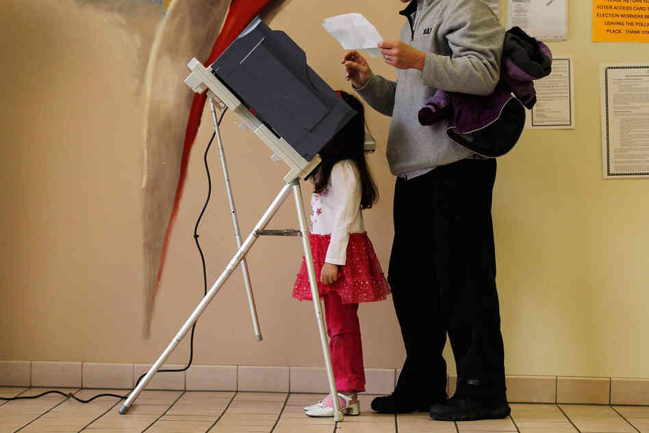 Sophia Walsh, 5, watches as her father, William Walsh, fills out his ballot in Steubenville, Ohio.