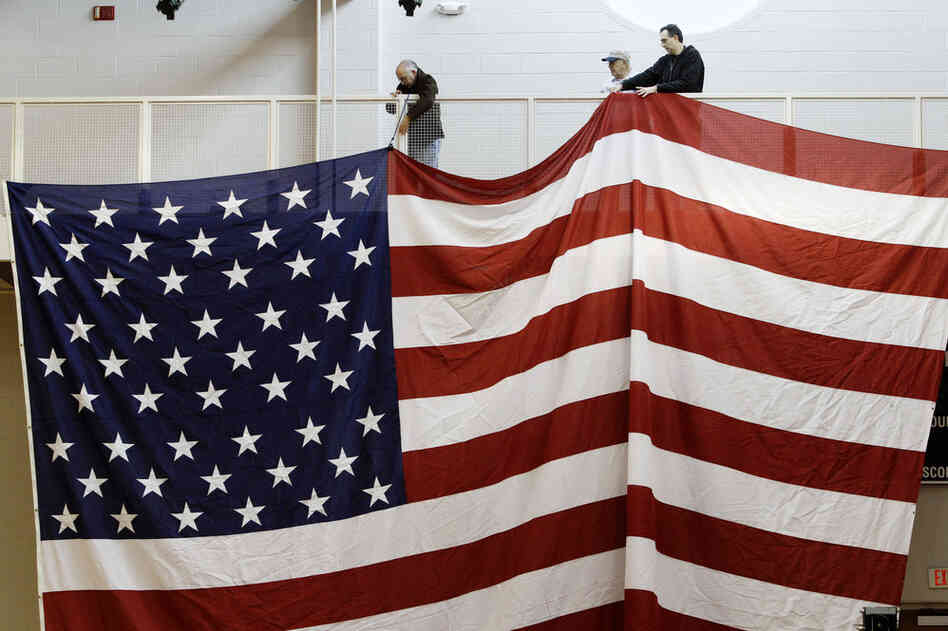 Workers hang an American flag in preparation for Santorum's election night party at Steubenville High School in Steubenville, Ohio.
