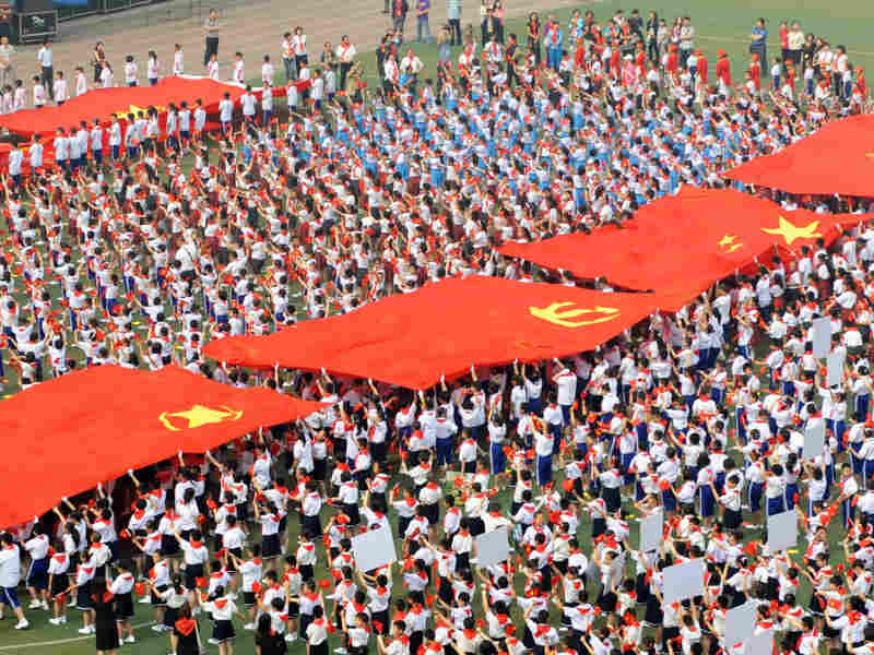 Thousands of Chinese students holding Communist flags gather to mark the 90th anniversary of the founding of China's Communist Party at a school in Taiyuan, north China's Shanxi province on May 30, 2011.