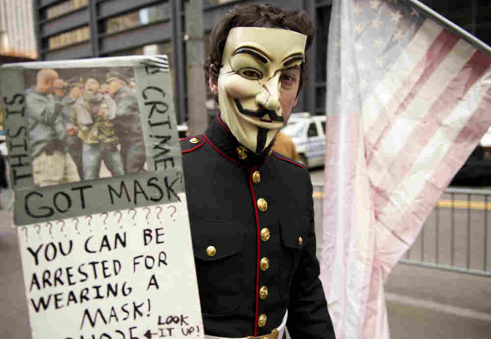 A young man with wearing a military uniform and mask usually associated with the group anonymous marches with Occupy Wall Street protesters in this November.