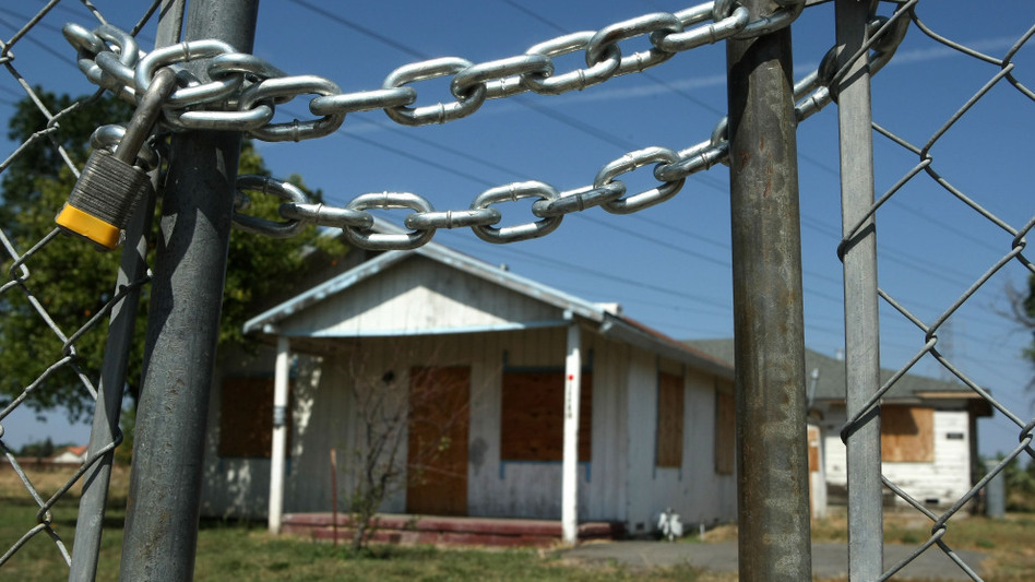 An abandoned home sits behind a padlocked gate in Stockton, Calif., in 2008.