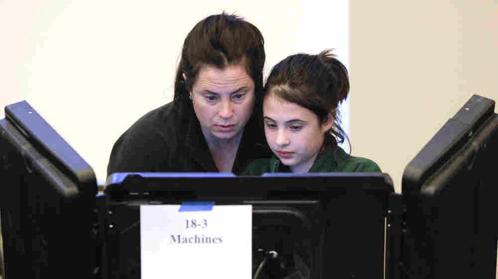 Sally Tepper, 12, watches her mother, Dana, vote in Nashville, Tenn., on Tuesday. Pew experts say Romney trails Obama among women, 38 to 59 percent.