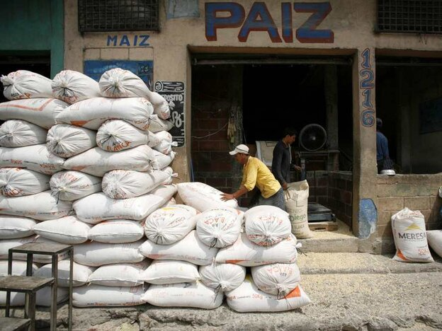 A worker piles sacks of corn at a market in Guatemala City.
