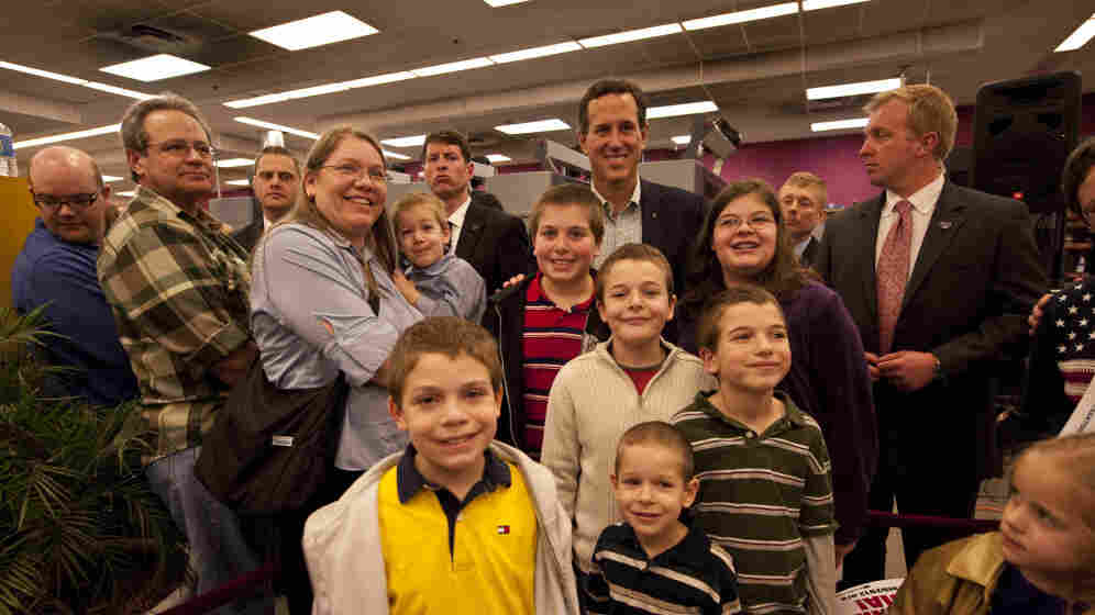 Rick Santorum poses with people at Harvest Graphics, a small business, during a campaign stop Wedneday in Lenexa, Kansas.