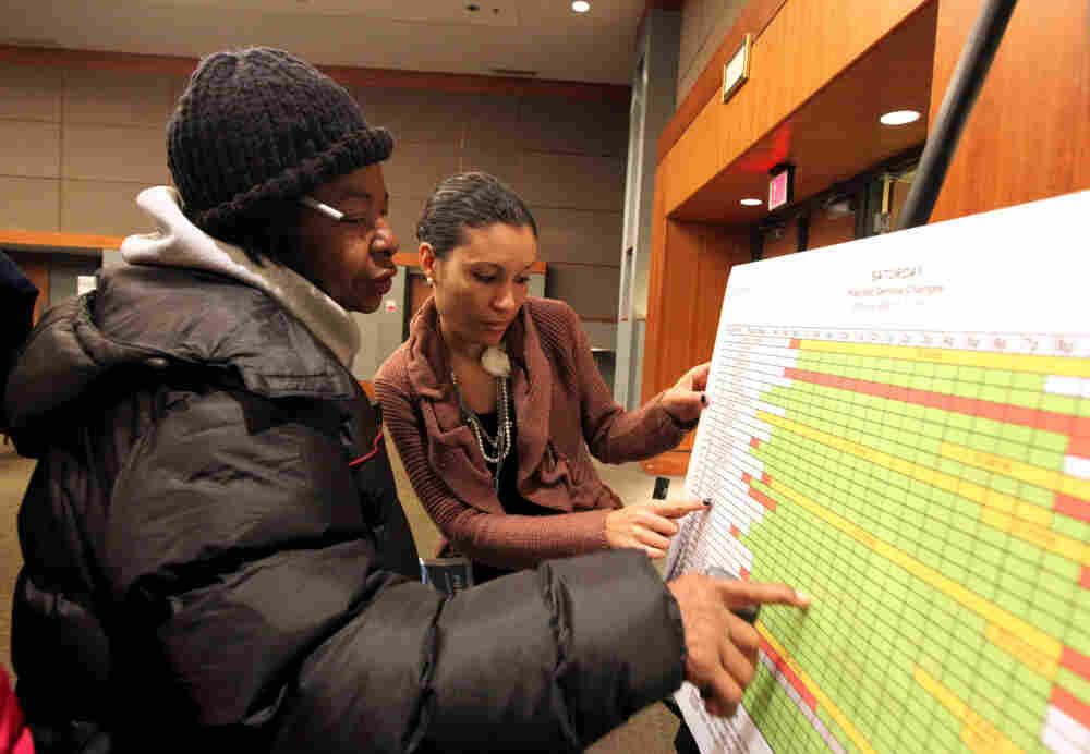 Gladys Ferguson, of Detroit, looks on as SuVon Treece of the Detroit Department of Transportation explains the new service schedule. A public hearing discussed future Detroit Department of Transportation bus service at the Northwest Activity Center on Feb. 24.