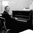 Jerry Lee Lewis smiles over his shoulder while playing the piano in a dressing room.