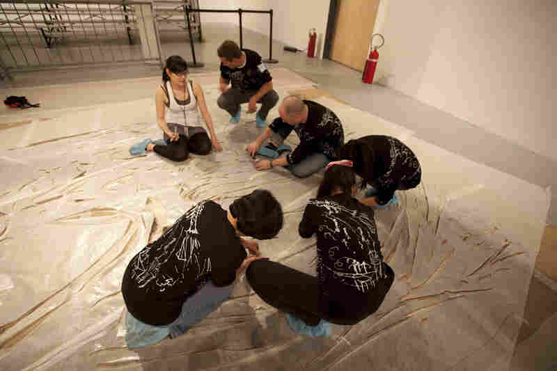Before the explosion, volunteers help prepare the enormous canvases with cardboard stencils.