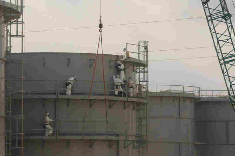 Workers assemble water tanks at the power station on Feb. 20. Engineers plan to flood the reactors, which will give them safe access to the nuclear fuel.