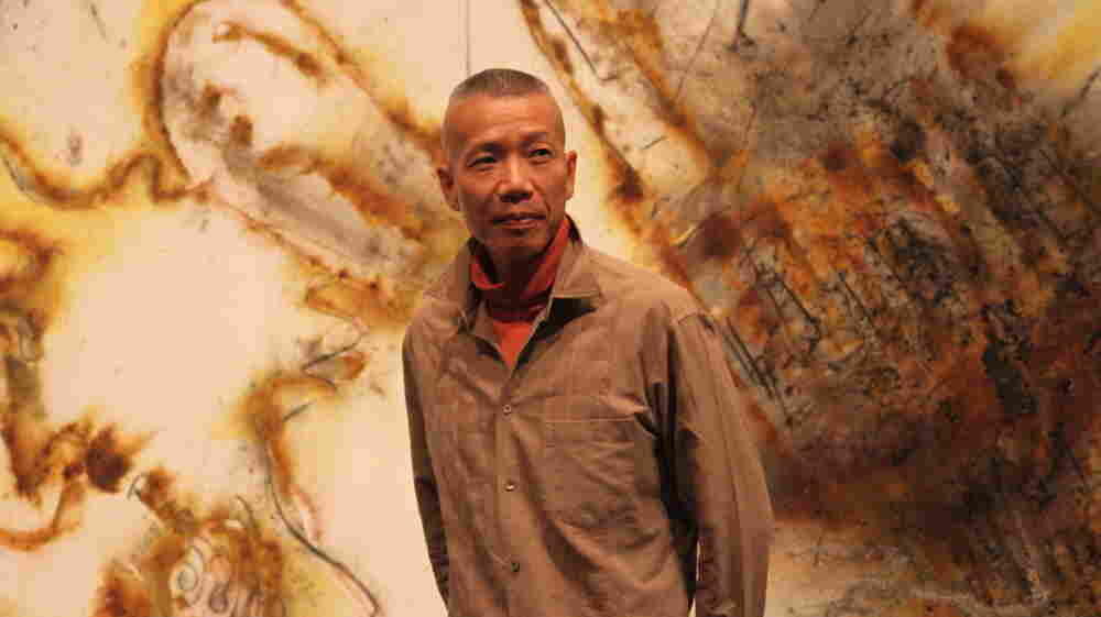 Artist Cai Guo-Qiang stands in front of a gunpowder drawing, Desire for Zero Gravity, at The Museum of Contemporary Art in Los Angeles. Cai uses a pyrotechnic process to burn shapes into large-scale canvases.