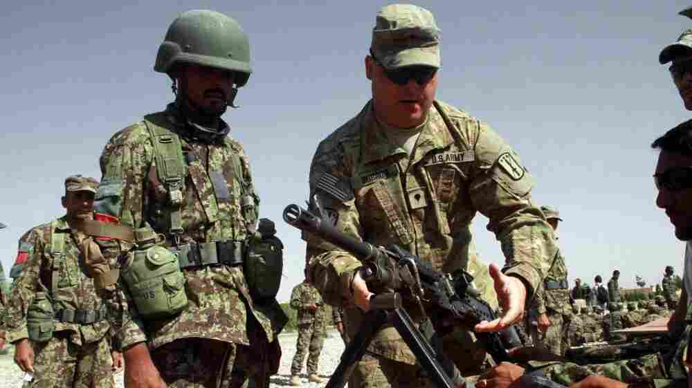 A U.S. soldier instructs Afghan soldiers in the western city of Herat last July. Afghans in security force uniforms have killed a number of U.S. and NATO troops recently. The shootings come as NATO works to prepare the Afghan forces to take control of security.