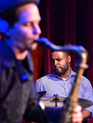Kendrick Scott, through the crook of John Ellis' saxophone.