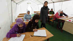 Syrian girls attend a class in a makeshift classroom at a refugee camp on the Turkish-Syrian border in southern Turkey's Hatay province, on Feb. 8. More than 12,000 Syrians live in refugee camps in Hatay, and several thousand more have found accommodations elsewhere.